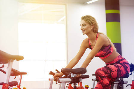 Beautiful young sporty woman on exercise bike in gym. Pretty woman working out indoors at fitness studio.Fitness. Healthy lifestyle.