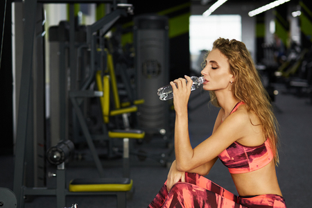 Beautiful young sporty woman sitting on exercise machine in gym. Break after hard workout. Fitness. Young girl at the gym trainer holding a bottle of water. Healthy lifestyle.