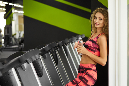 Beautiful young sporty woman resting after hard workout in gym. Fitness woman holding bottle of water at fitness studio. Fitness. Healthy lifestyle. Stock Photo