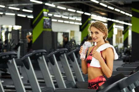 Beautiful young sporty woman resting after hard workout in gym. Fitness woman holding bottle of water at fitness studio. Fitness. Healthy lifestyle. Standard-Bild