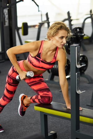 Beautiful young sporty woman doing sport exercises on exercise machine in gym. Fitness. Pretty woman working out indoors at fitness studio. Fitness. Healthy lifestyle.