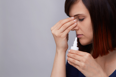 Closeup portrait of young woman on grey background suffering from runny nose and allergy, holding fingers to nose and prepairing to use nasal spray.