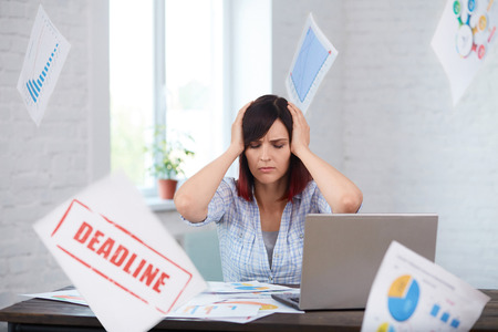 Tired disturbed female worker with headache and falling papers around. Stressed woman in office holding head in hands and thinking about deadline. Overwork,burnout,negative thoughts,deadline concept. Imagens