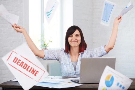 Happy and smiling female worker throws documents in office with falling papers around.Finishing work in time.Time management, deadline concept. Stock Photo