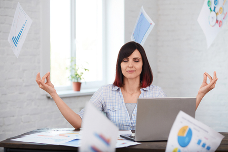 Tired female worker meditates in office with falling papers around.Stressed woman trying to calm down and not thinking about deadline.Overwork, deadline concept. Stock Photo