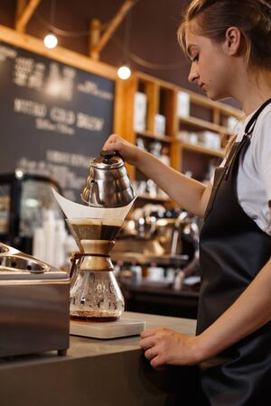 Professional barista preparing coffee using pour over coffee maker and drip kettle. Young woman making coffee. Alternative ways of brewing coffee. Coffee shop concept.