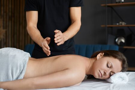 Young beautiful woman enjoying back and shouders massage in spa.Professional massage therapist is treating a female patient in apartment.Relaxation,beauty,body and face treatment concept.Home massage.