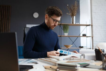Architect working in office with color palette. Engineer select colors for building using color swatches, searching new ideas for construction project. Portrait of handsome bearded man at workplace.