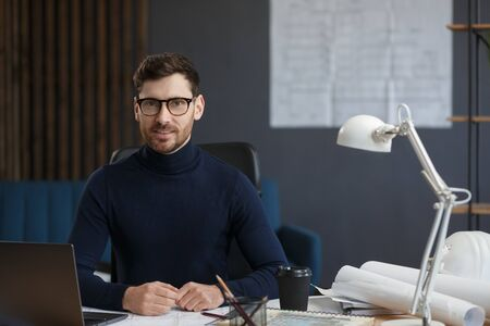 Architect working in office with laptop. Business portrait of handsome bearded man wearing eyeglasses sitting at workplace. Confident businessman became successful. Business concept.