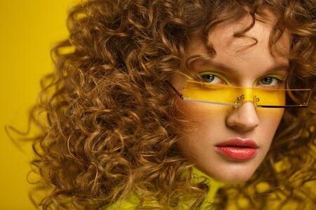 Close up fashion studio portrait of young beautiful women with curly hair. Nice girl with afro hair and bright make up wearing yellow eyeglasses over yellow background. Beauty and hair care concept.