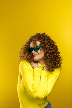 Beauty and hair care concept. Fashion studio portrait of young beautiful women with curly hair. Nice girl with afro hair and bright make up wearing green eyeglasses standing on yellow background.