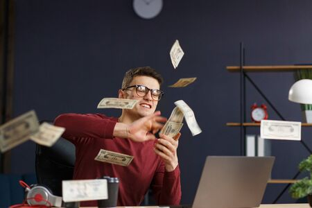 Im rich. Portrait of a young freelancer or businessman in a home office. Throws cash. Successful deal. Earnings online. Win the money.