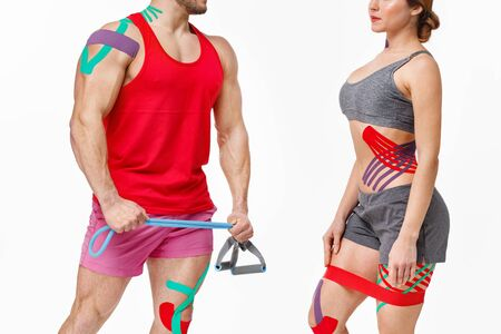 Kinesiology taping. Post traumatic rehabilitation, sport physical therapy, recovery concept. Two young male athletes doing exercises with expender.Kinesiology tape on patient knee, shoulder,neck,hip.