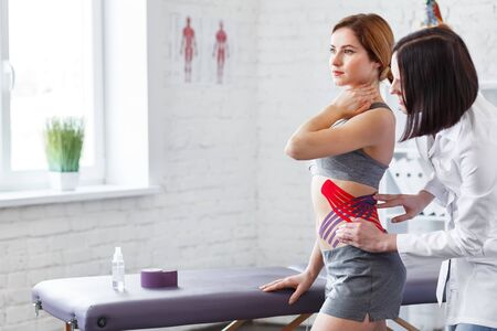 Weight loss concept.Kinesiology taping.Therapist applying kinesiology tape to patient belly.Anti-cellulite procedure for slim tummy.Fat lose,cellulite removal, sport physical therapy,recovery concept. Foto de archivo