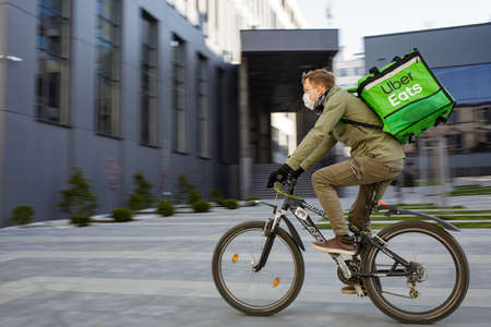 Food supplier with Uber Eats backpack riding a bike on the street. A masked courier delivers food in a pandemic.