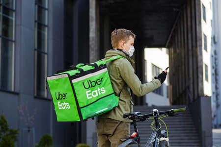 Ukraine. LvivÑŽ 03/05/2020. Food supplier with Uber Eats backpack riding a bike on the street. A masked courier delivers food in a pandemic.