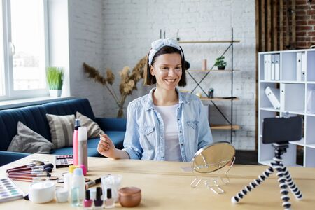 Young female blogger recording a tutorial video for her beauty blog about cosmetics.Vlogger testing eye pads and broadcast live video to social network at home. Blogging, videoblog, skincare concept.