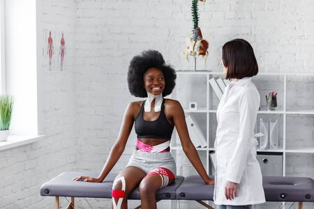 Young female African American athlete visiting physiotherapist. Kinesiology taping. Anti-cellulite procedure, fat lose, cellulite removal, post traumatic rehabilitation,sport physical therapy. Banque d'images