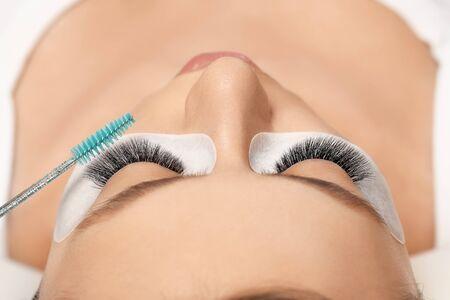 Eyelashes extensions. Fake eyelashes. Eyelash extension procedure.Close up portrait of woman eye with long eyelashes. Professional stylist lengthening female lashes. Master and client in beauty salon. Banque d'images