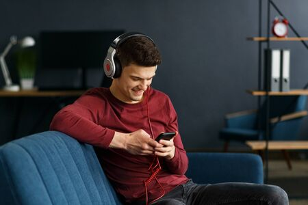 Enjoy listening to music.Young man in headphones listening music on smart phone using music app. Portrait of guy in earphones and mobile phone at home. Relaxation, leisure and stress management.