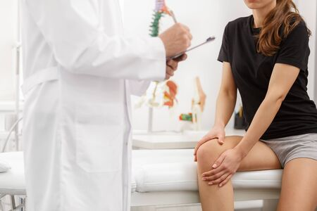 Male doctor examining female patient suffering from knee pain. Medical exam. Chiropractic, osteopathy, post traumatic rehabilitation, sport physical therapy. Alternative medicine, pain relief concept.