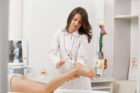 Achilles tendinitis. Neurologist testing reflex using reflex hammer. Neurological physical examination. Orthopedist work. Medical research. Diagnostic, healthcare, medical service.