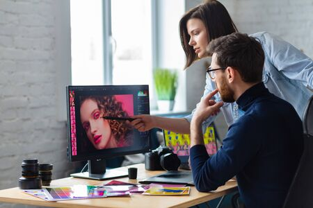 Professionals - photographer and retoucher. Retouching images on a graphics tablet. Teamwork in a professional photo studio.
