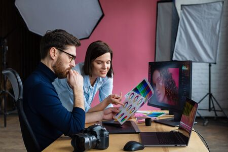 Professionals - photographer and retoucher. Retouching images on a graphics tablet. Teamwork in a professional photo studio. Stock Photo