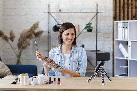 Young female blogger recording a tutorial video for her beauty blog about cosmetics.Vlogger testing eyeshadow and broadcast live video to social network at home.Blogging, videoblog, makeup concept.
