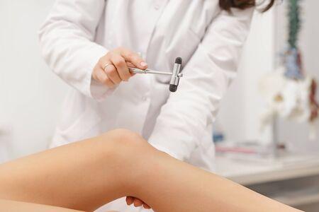 Neurologist testing knee reflex using reflex hammer. Neurological physical examination. Orthopedist work. Medical research. Diagnostic, healthcare, medical service.