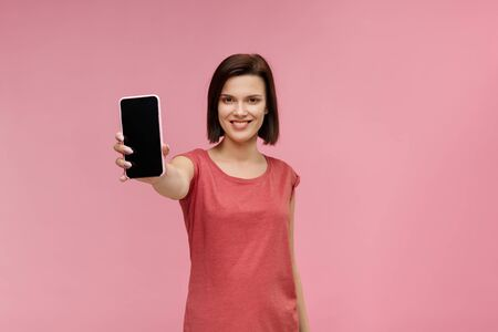 Funny brunette woman showing blank screen mobile phone on camera. Young smiling girl demonstrating smartphone display isolated over pink background. Copy space. App for your business.