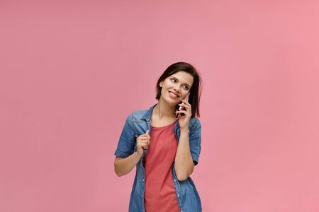 Young people working with mobile devices. Portrait of cute happy brunette woman wearing t-shirt and jeans shirt talking on mobile phone and smiling isolated over pink background. Copy space.