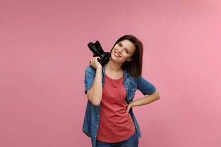 Portrait of young female photographer isolated on pink background with copy space. Photographer with professional camera taking photo in photo studio. Profession, occupation, self-employment.
