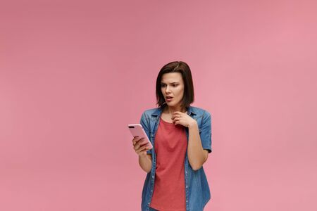 Surpised young brunette woman holding pink smartphone, smiling and expressing positivity. Happy girl got shocking positive news. Copy space. Young people working with mobile devices.