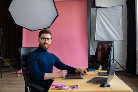 Retouching images in special program.Portrait of graphic designer working in office with laptop,monitor,graphic drawing tablet and color palette.Retoucher workplace in photo studio.Creative agency.