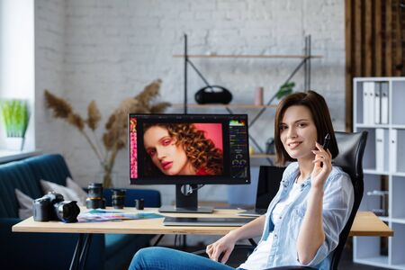 Portrait of graphic designer working in office with laptop,monitor,graphic drawing tablet and color palette.Retouching images in special program.Retoucher workplace in photo studio.Creative agency. 版權商用圖片