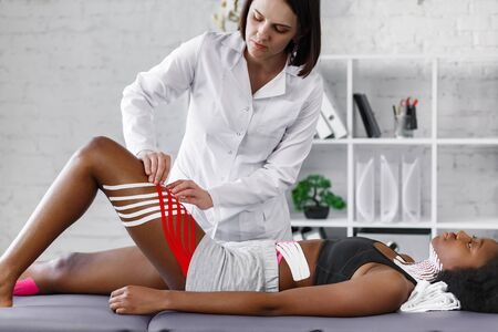 Kinesiology taping. Physiotherapist applying kinesiology tape to patient hips.Therapist treating young female African American athlete. Post traumatic rehabilitation, fat lose,sport physical therapy.
