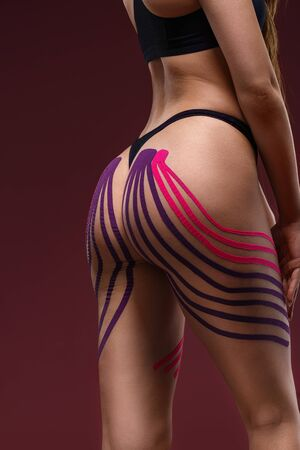 Close up view of kinesiology tape on tight buttocks. Kinesiology taping. Weight loss concept. Anti-cellulite procedure for slim hips. Fat lose, cellulite removal, recovery concept. 版權商用圖片
