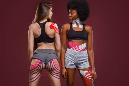 Kinesiology taping. Two young female athletes on red background with kinesiology tape on neck,shoulder, khee, tummy and hips. Fat lose, cellulite removal, sport physical therapy,recovery concept.