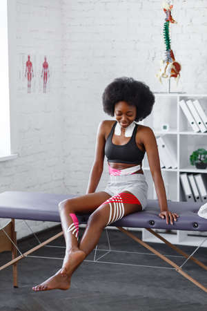 Young female African American athlete visiting physiotherapist. Kinesiology taping. Anti-cellulite procedure, fat lose, cellulite removal, post traumatic rehabilitation,sport physical therapy. Foto de archivo