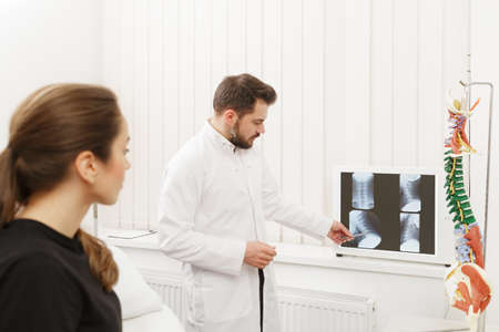 Doctor showing results of X-ray examination to his patient and explains the cause of her pain in medical office. Patient visiting physiotherapist in clinic. Surgery, healthcare and medicine concept.