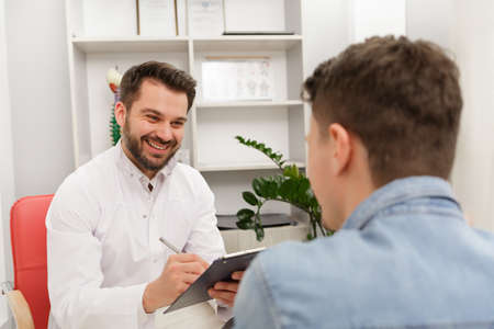 Doctor and patient in medical office. Therapist talking to patient in office, taking notes, writing prescription. Consultation in clinic. Healthcare and medicine concept. 版權商用圖片