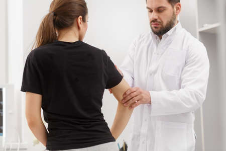 Male doctor examining female patient suffering from elbow pain. Medical exam. Chiropractic, osteopathy, post traumatic rehabilitation,sport physical therapy. Alternative medicine, pain relief concept.