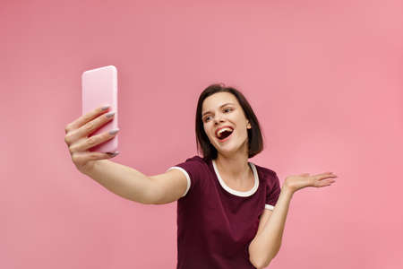 Funny young brunette woman making selfie. Smiling girl wearing t-shirt holding pink smartphone, making faces on camera, posing for selfie isolated on pink background.