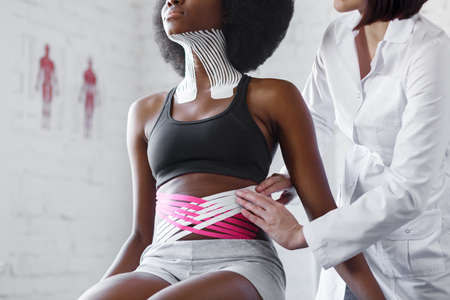 Weight loss concept.Kinesiology taping.Therapist applying kinesiology tape to patient belly.Anti-cellulite procedure for slim tummy.Fat lose,cellulite removal, sport physical therapy,recovery concept.