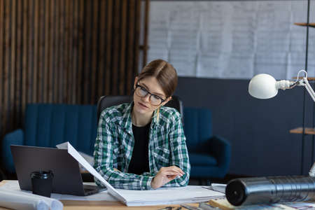 Female interior designer working in office with laptop. Architect thinks over architectural plan, searching new ideas for construction project. Woman sitting at workplace. Business portrait concept.