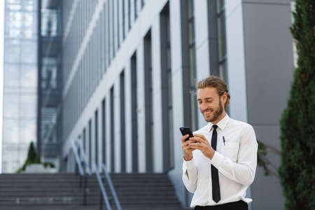 Portrait of a successful young businessman. A curly-haired man in a white shirt with a telephone against the background of a modern business center. Banque d'images