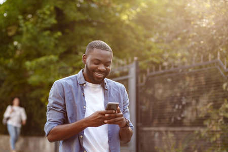Handsome Afro-American man using smartphone and smiling. Happy man using mobile phone apps, texting message, browsing internet, looking at smartphone. Young people working with mobile devices.
