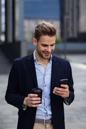 Handsome office worker holding smartphone and smiling. Happy young man using mobile phone apps, texting message, browsing internet, looking at smartphone. Coffee break near the business center.