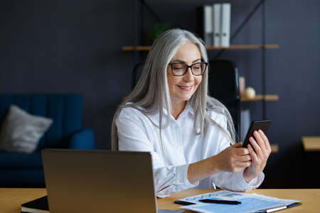 Senior grey-haired beautiful woman using smartphone and smiling. Happy businesswoman using mobile phone apps, texting message, browsing internet, shopping online. Mature people with mobile devices. Foto de archivo